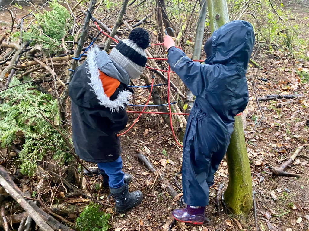 Working cooperatively to build a den in the woods using grappling hooks