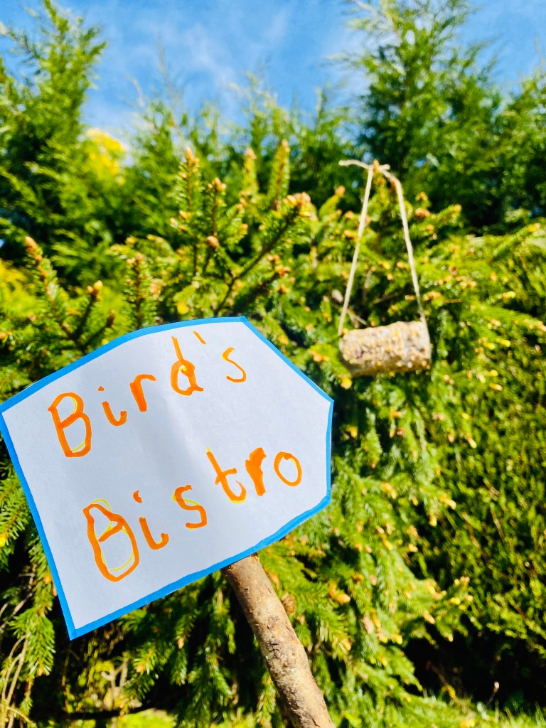 Homemade bird-feeders with sign that reads 'Bird's Bistro'